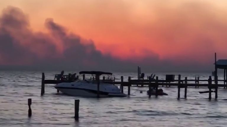 Wildfires rage in the background at Santa Rosa Beach in Florida