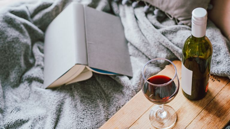 Shot of a glass of red wine and a book on the bed at home