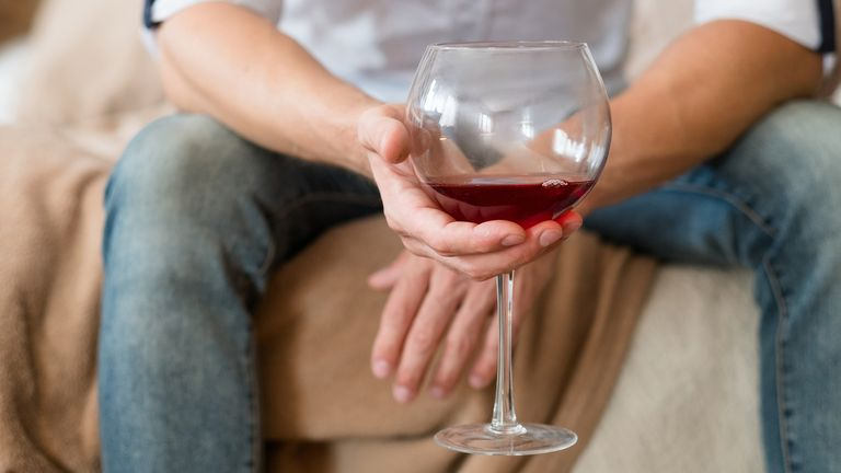 Problem, depression. Alcohol abuse. Man sitting with half empty red wine glass. Cropped shot. Home solitude.