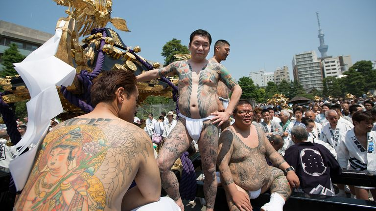 Heavily-tattooed Takahashi-gumi gang members are seen at a festival in Tokyo in 2012