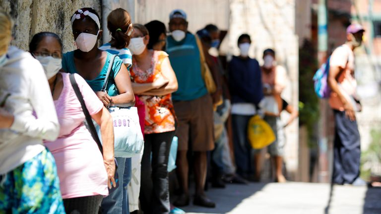 People queue for food from a charity in a slum in Caracas, Venezuela, where the poverty-stricken country's economy has been crippled further by COVID-19