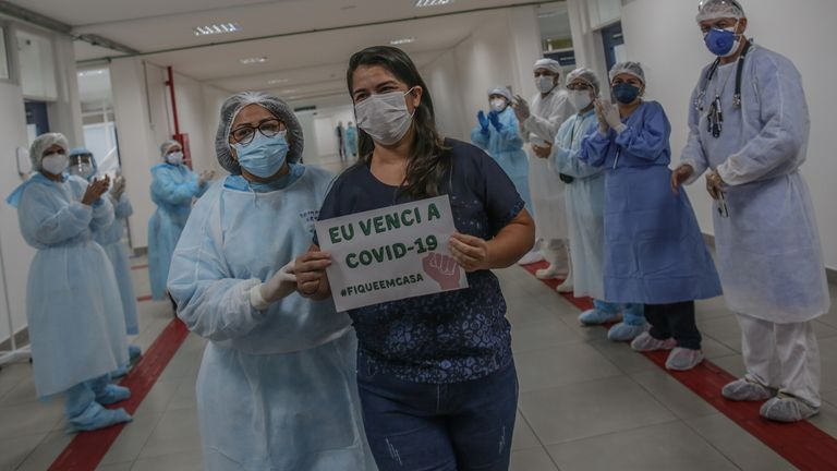 A patient holds a sign that reads 'I beat the COVID-19 #StayAtHome' at a hospital in Manaus, Brazil