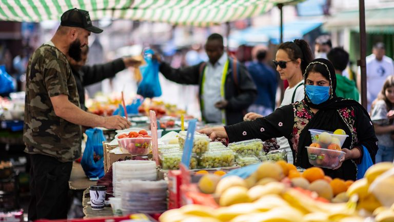 LONDON, UNITED KINGDOM - MAY 26: A member of the public shops for fruit and vegetables at Walthamstow Street Market on May 26, 2020 in London, England. The British government continues to ease the coronavirus lockdown by announcing schools will open to reception year pupils plus years one and six from June 1st. Open-air markets and car showrooms can also open from the same date. (Photo by Justin Setterfield/Getty Images)