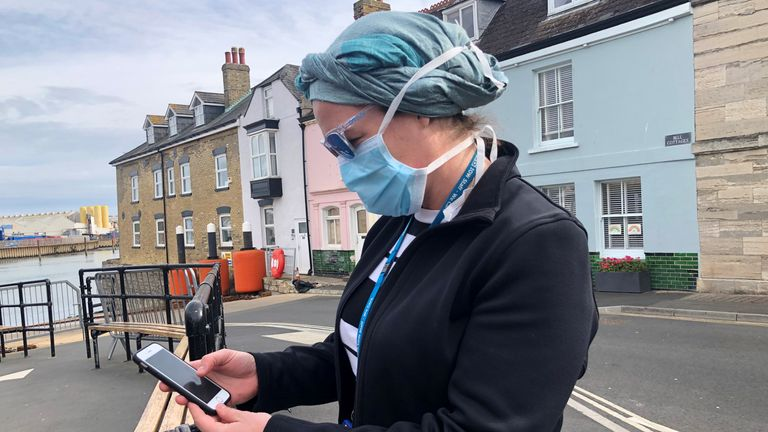 UK National Health Service employee Anni Adams looks at new NHS app to trace contacts with people potentially infected with the coronavirus disease (COVID-19) being trialled on Isle of Wight. Pic: Reuters