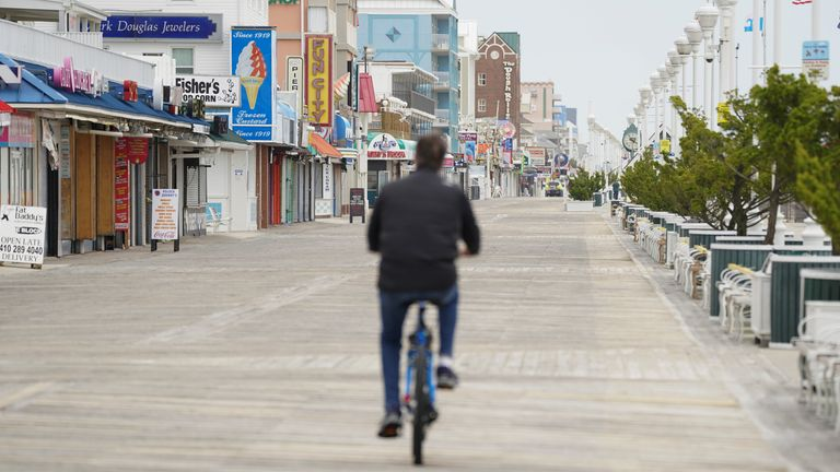 A man cycles along the boardwalk, a day before the coronavirus disease (COVID-19) restrictions are relaxed in Ocean City, Maryland, U.S., May 8, 2020. REUTERS/Kevin Lamarque