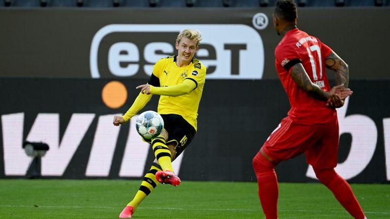Bayern Munich's defender Jerome Boateng (R) reacts as Dortmund's Julian Brandt has a shot