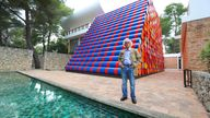 """Bulgarian artist Christo poses in front of the monumental """"Mastaba"""" art work at the Maeght Foundation (Fondation Maeght) on the opening day of the exibition on June 4, 2016 in Saint-Paul-de-Vence, southeastern France"""