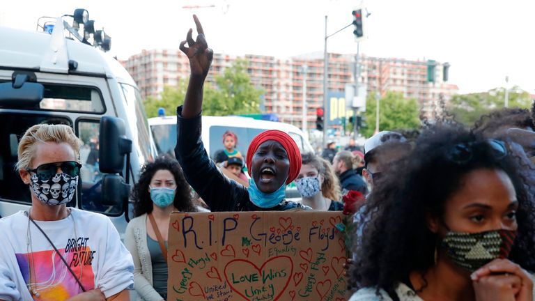 A woman holding a placard for George Floyd in front of the US Embassy at a protest in Berlin, on May 30, 2020. - Violent protests erupted across the United States late on May 29 over the death of a handcuffed black man in police custody, with murder charges laid against the arresting Minneapolis officer failing to quell seething anger. (Photo by Odd ANDERSEN / AFP) (Photo by ODD ANDERSEN/AFP via Getty Images)