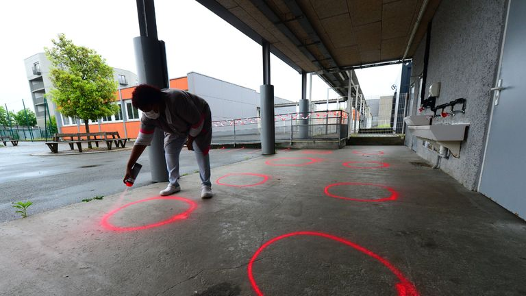 An agent draws distance marks on the ground of the courtyard at Jean-Jaures elementary school in Cenon near Bordeaux, southwestern France on May 11, 2020 amid preparations to re-open primary schools, on the first day of France's easing of lockdown measures in place for 55 days to curb the spread of the COVID-19 pandemic, caused by the novel coronavirus. (Photo by MEHDI FEDOUACH / AFP) (Photo by MEHDI FEDOUACH/AFP via Getty Images)