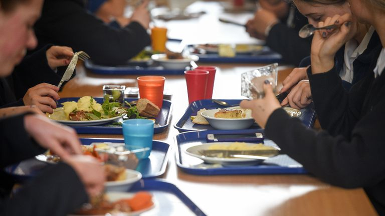 Students eat their school dinner from trays and plates during lunch in the canteen at Royal High School Bath, which is a day and boarding school for girls aged 3-18 and also part of The Girls' Day School Trust, the leading network of independent girls' schools in the UK.