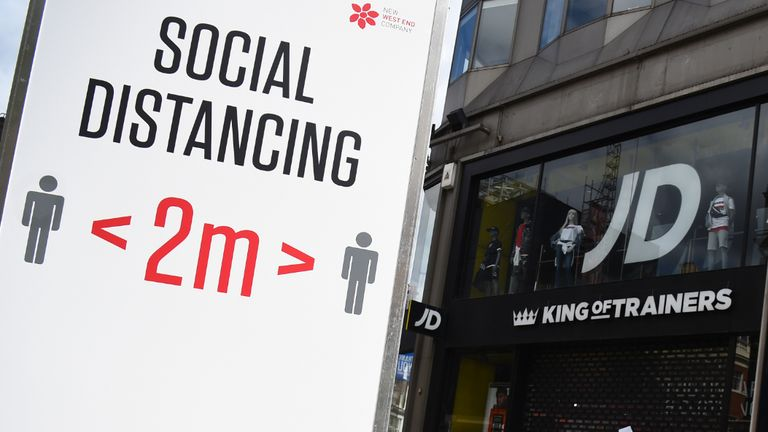 People walk pass social distancing signage on Oxford Street, London, ahead of the re-opening of non-essential retailers in England on June 15.