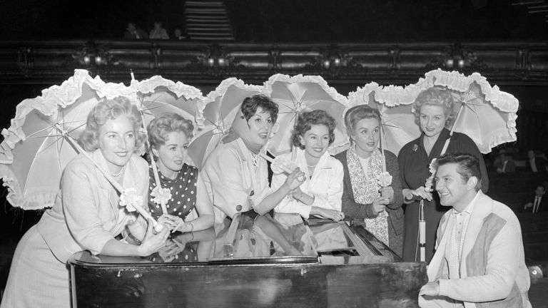 American pianist Liberace, surrounded by (l-r) Vera Lynn, Marion Ryan, Alma Cogan, Janette Scott, Yana and Anne Shelton. They were all attending a rehearsal of the Royal Variety Show at the Victoria Palace, London.