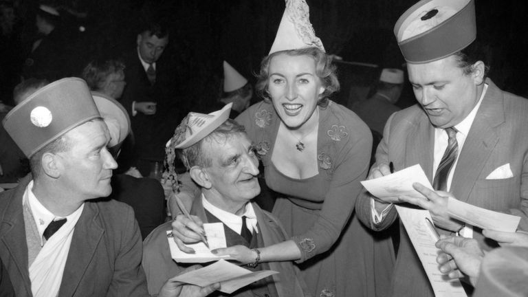 File photo dated 13/12/56 of singer Vera Lynn and comedian Harry Secombe (right) signing autographs at the tea tables during the 'Not Forgotten' Association annual Christmas party, at the Royal Riding School, Buckingham Palace. Forces sweetheart Dame Vera Lynn has died at the age of 103.