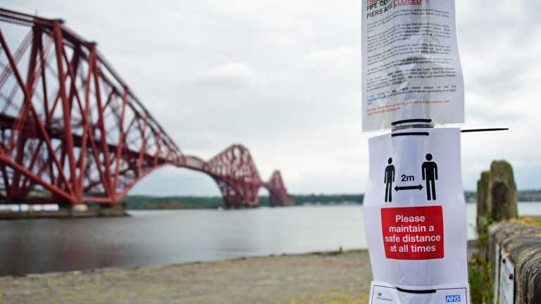 "NORTH QUEENSFERRY, SCOTLAND - JUNE 9: Posters with Covid-19 regulations and advice on a road sign at the Town Pier with the Forth Bridge in the background, after the the Scottish Government eased some Covid-19 lockdown restrictions over the past week, whilst maintaining ""Stay At Home"" as the core message, on June 9, 2020 in North Queensferry, Scotland. Scotland is due to review its restrictions put in place to curb the coronavirus on June 18. First Minister Nicola Sturgeon has said she is optimistic that more restrictions will be lifted following a decline in the number of deaths caused by COVID-19. (Photo by Ken Jack/Getty Images)"