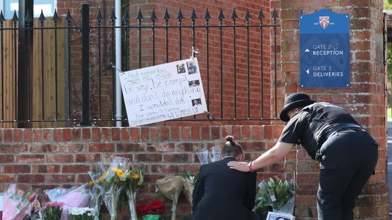 A mourner is comforted by a police officer as they place flowers at the entrance to the Holt School, Wokingham, Berskhire, in tribute to teacher James Furlong, a victim of the terrorist attack in Forbury Gardens, Reading, on Saturday in which three people died.
