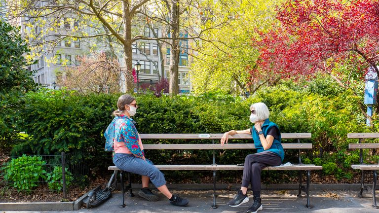 Manhattan, New York, USA - 5/2/2020: Senior women pratcing social distancing in Madison Square park while sitting on park bench during covid-19 pandemic lockdown.