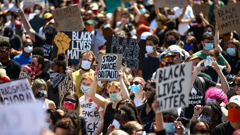"""LONDON, ENGLAND - MAY 31: People hold placards as they join a spontaneous Black Lives Matter march at Trafalgar Square to protest the death of George Floyd in Minneapolis and in support of the demonstrations in North America on May 31, 2020 in London, England. The death of an African-American man, George Floyd, at the hands of police in Minneapolis has sparked violent protests across the USA. A video of the incident, taken by a bystander and posted on social media, showed Floyd's neck being pinned to the ground by police officer, Derek Chauvin, as he repeatedly said """"I can't breathe"""". Chauvin was fired along with three other officers and has been charged with third-degree murder and manslaughter. (Photo by Hollie Adams/Getty Images)"""