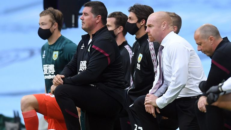 Burnley's English manager Sean Dyche (2R) takes a knee in support of the Black Lives Matter movement ahead of the English Premier League football match between Manchester City and Burnley at the Etihad Stadium in Manchester, north west England, on June 22, 2020. (Photo by Michael Regan / POOL / AFP) / RESTRICTED TO EDITORIAL USE. No use with unauthorized audio, video, data, fixture lists, club/league logos or 'live' services. Online in-match use limited to 120 images. An additional 40 images may be used in extra time. No video emulation. Social media in-match use limited to 120 images. An additional 40 images may be used in extra time. No use in betting publications, games or single club/league/player publications. /  (Photo by MICHAEL REGAN/POOL/AFP via Getty Images)