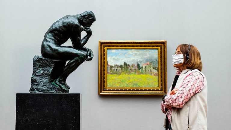 "TOPSHOT - A visitor wearing a face mask looks at French sculptor Auguste Rodin's iconic sculpture ""The Thinker"" at the Alte Nationalgalerie (Old National Gallery) museum in Berlin on May 12, 2020, after the museum re-opened its doors to the public following a relaxation of lockdown restrictions due to the new coronavirus COVID-19 pandemic. (Photo by John MACDOUGALL / AFP) / RESTRICTED TO EDITORIAL USE - MANDATORY MENTION OF THE ARTIST UPON PUBLICATION - TO ILLUSTRATE THE EVENT AS SPECIFIED IN THE CAPTION (Photo by JOHN MACDOUGALL/AFP via Getty Images)"