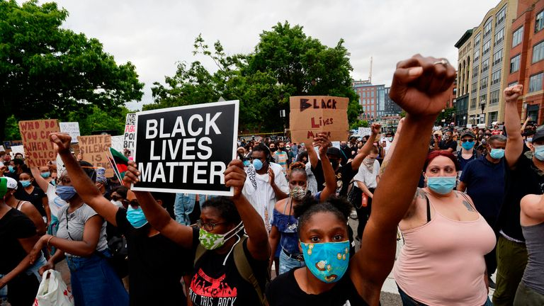 Protesters hold signs as they gather to protest police brutality and racism in the US, with the recent deaths of George Floyd, Ahmaud Arbery, Breonna Taylor, in Boston, Massachusetts, on May 29, 2020. - The Minneapolis police officer accused of killing George Floyd, a handcuffed African American man, was charged with murder on May 29 as authorities declared a curfew after three nights of violent protests left parts of the city in flames. (Photo by Joseph Prezioso / AFP) (Photo by JOSEPH PREZIOSO/AFP via Getty Images)