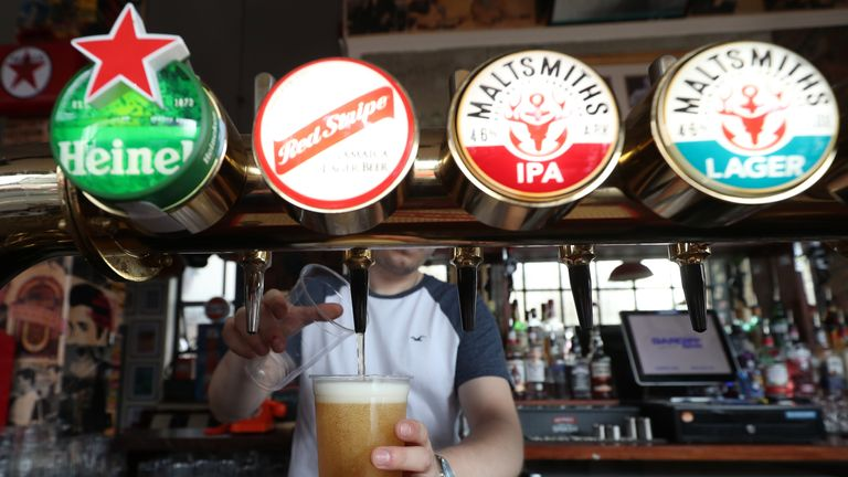 A barman serving takeaway drinks at Charrington's Noted Ales And Stout pub in London, as further coronavirus lockdown restrictions are lifted in England.