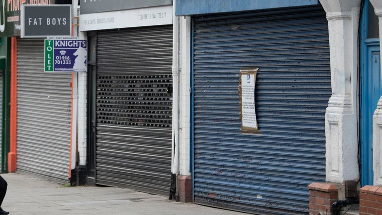 BARRY, UNITED KINGDOM - JUNE 12: A man and woman look at closed shops on during the coronavirus lockdown period on June 12, 2020 in Barry, United Kingdom. GDP fell by 20.4% in April, compared with the previous month, according to data from the Office for National Statistics. At the end of April the economy was about 25 per cent smaller than in February. The Welsh government has further relaxed COVID-19 lockdown measures this week, allowing people from different households to meet up outside while maintaining social distancing. Schools have remained closed and those who have been advised to shield at home can go outside again but have been told to avoid shopping. (Photo by Matthew Horwood/Getty Images)