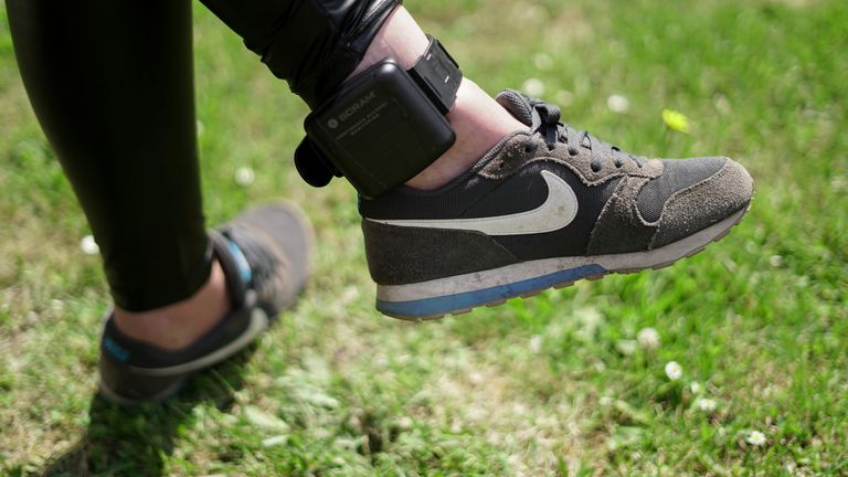 "An unidentified woman displays an ankle strap, called ""alcoholmeter"", that can measure alcohol consumption from sweat due to control consumption of people who have been convicted for a crime and whose sentence includes a ban on alcohol consumption, in Zutphen, Netherlands June 12, 2020"
