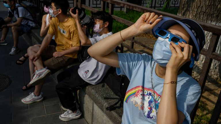 BEIJING, CHINA - JUNE 21: A Chinese woman wears a protective mask to prevent COVID-19 and protective glasses as she watches the sun during the annular solar eclipse outside the Forbidden City on June 20, 2020 in Beijing, China. The eclipse's path of totality, when the earth, moon and sun are aligned, passed from west to east over 12 countries and coincided with the arrival of the summer solstice.Authorities are trying to contain the outbreak linked to the Xinfadi wholesale food market, Beijing's