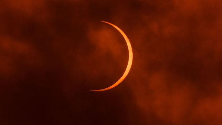 The moon moves in front of the sun during an annular solar eclipse as seen through clouds from New Delhi on June 21, 2020. (Photo by Jewel Samad / AFP) (Photo by JEWEL SAMAD/AFP via Getty Images)