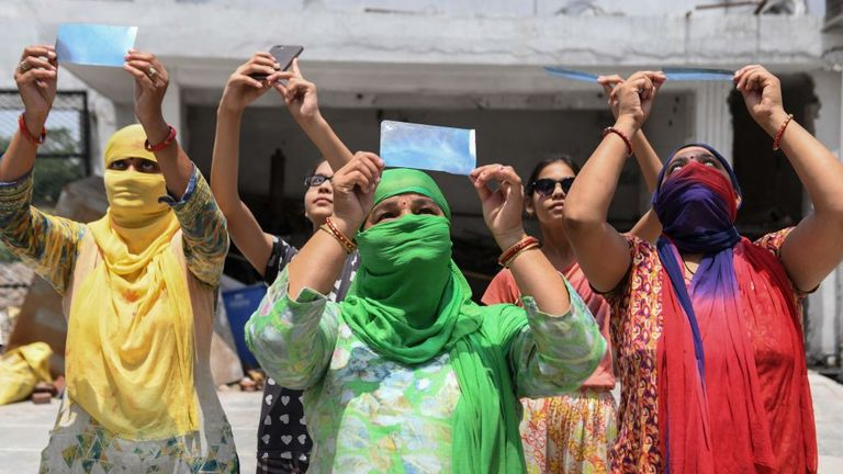Hindu devotees observe an annular solar eclipse through X-Ray films atDurgiana Temple in Amritsar on June 21, 2020. (Photo by NARINDER NANU / AFP) (Photo by NARINDER NANU/AFP via Getty Images)