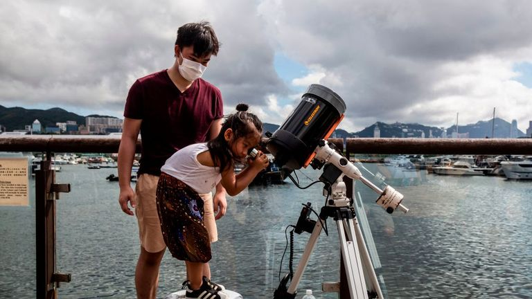 A child watches an annular solar eclipse through a telescope along a promenade in Hong Kong on June 21, 2020. (Photo by ISAAC LAWRENCE / AFP) (Photo by ISAAC LAWRENCE/AFP via Getty Images)