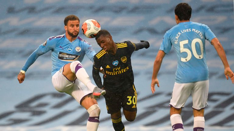 Arsenal's English striker Eddie Nketiah (C) vies for the ball against Manchester City's English defender Kyle Walker (L) during the English Premier League football match between Manchester City and Arsenal at the Etihad Stadium in Manchester, north west England, on June 17, 2020. - The Premier League makes its eagerly anticipated return today after 100 days in lockdown but behind closed doors due to coronavirus restrictions. (Photo by PETER POWELL / POOL / AFP) / RESTRICTED TO EDITORIAL USE. No