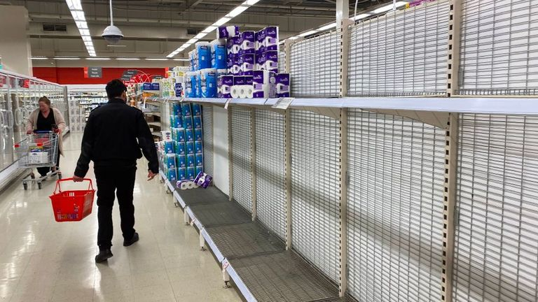 A shopper walks past near-empty shelves of toilet paper at a supermarket in a Melbourne on June 26
