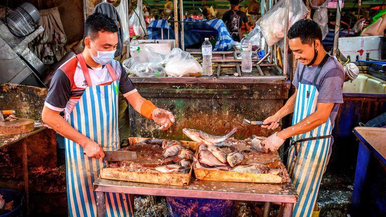 A man wears a mask at Khlong Toei Market in Bangkok