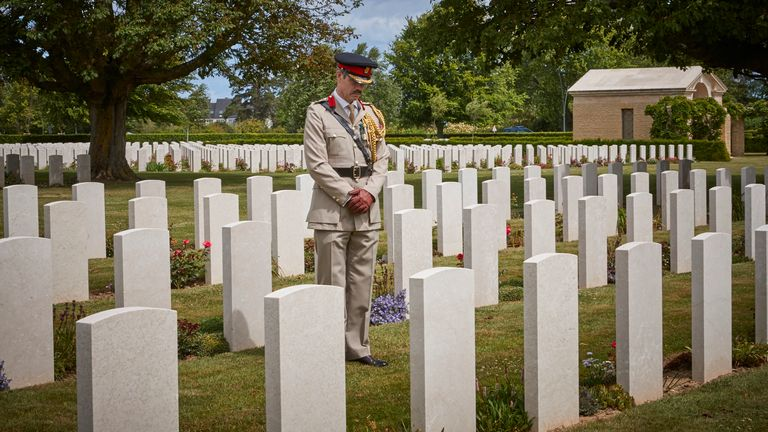 Colonel Howard Wilkinson stands amongst the graves at the Bayeux War Cemetery