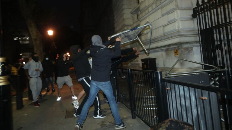 Protesters throw barricades at the gates of Downing Street