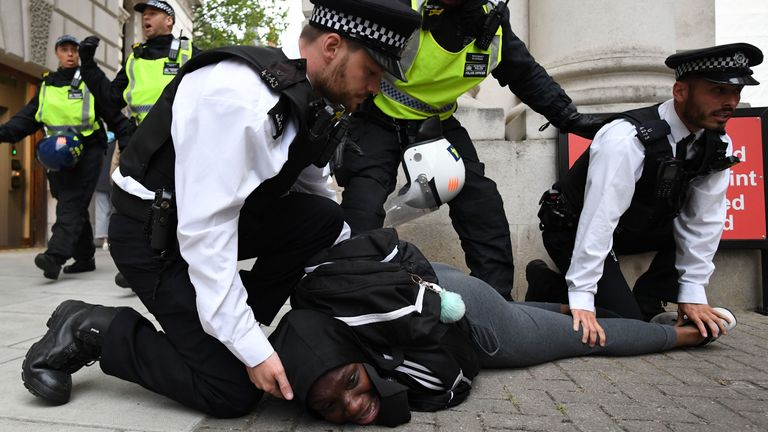 A man is detained by police officers in Whitehall