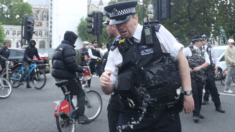 Police officers are spayed with a liquid in Parliament Square