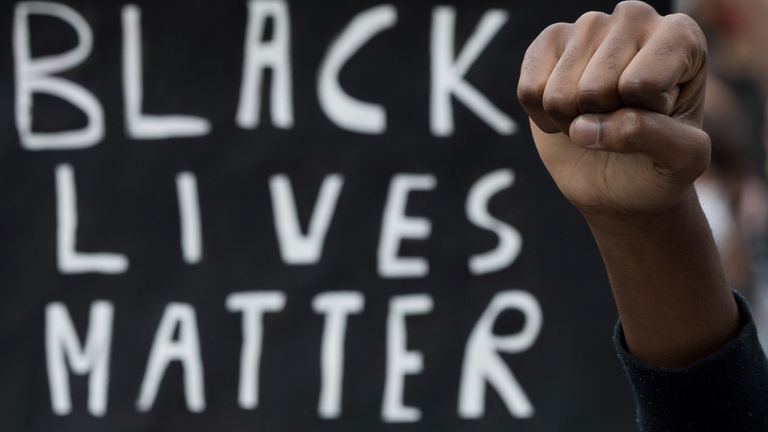 A demonstrator raises the fist next to a placard in Nantes, on June 8, 2020, during a 'Black Lives Matter' worldwide protests against racism and police brutality in the wake of the death of George Floyd, an unarmed black man killed while apprehended by police in Minneapolis