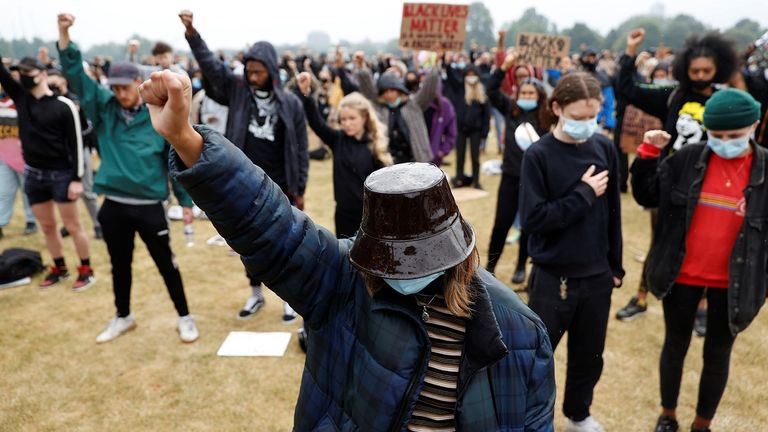 Protesters raise their fists in London's Hyde Park on Friday