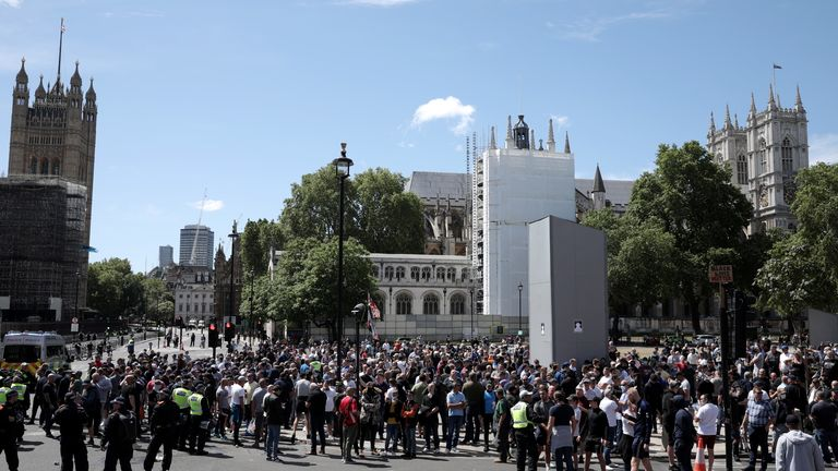 A crowd gathers around the Winston Churchill statue on Parliament Square