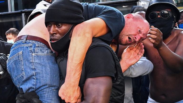 A protester carries an injured counter-protester to safety, near the Waterloo station during a Black Lives Matter protest