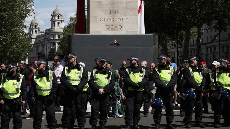 Police form a barrier in front of activists surrounding the Cenotaph