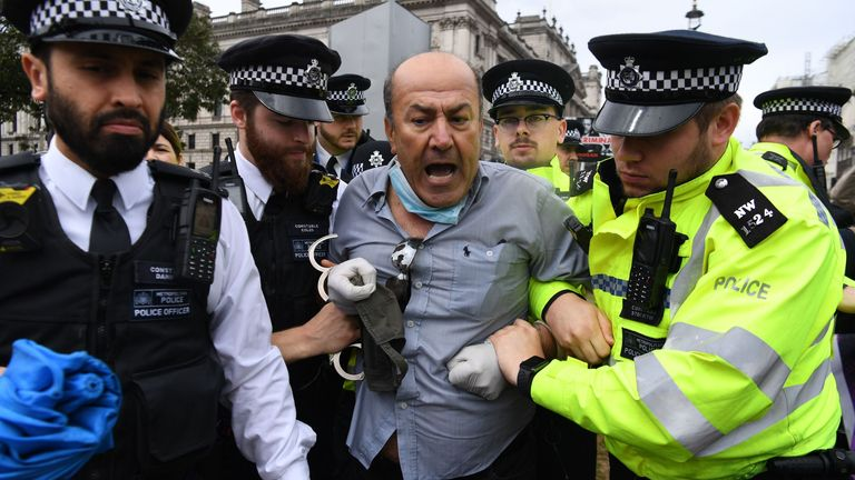 A pro-Kurdish protester who ran into the road toward the car of Britain's Prime Minister Boris Johnson as it was leaving the Houses of Parliament in London on June 17, 2020 is led away by police officers. - The protester ran into the road towards the Jaguar that normally carries the Prime Minister Boris Johnson and was stopped by police. As the Jaguar stopped it was subsequently struck from behind by the next vehicle in the convoy resulting in a large dent. (Photo by DANIEL LEAL-OLIVAS / AFP) (P