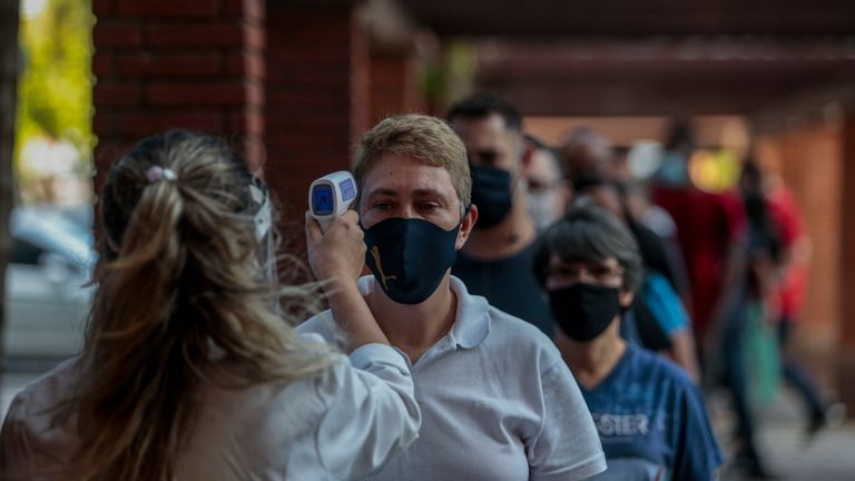 A shopper has his temperature measured during the first day of reopening stores on 11 June in Sao Paulo amidst the pandemic