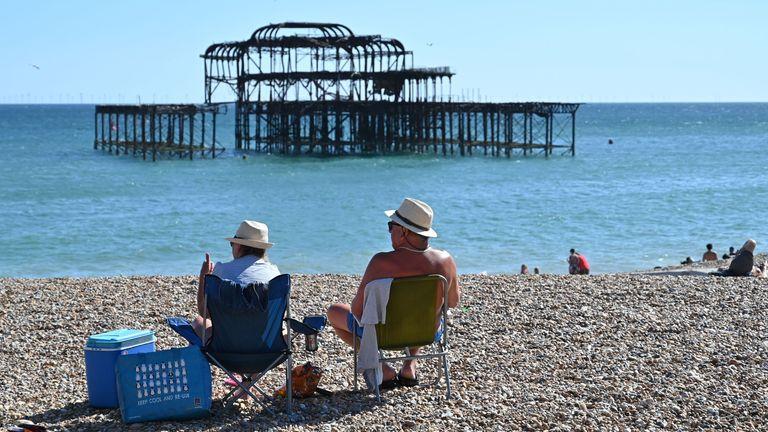 People sunbathe on the beach near the derelict West Pier in Brighton