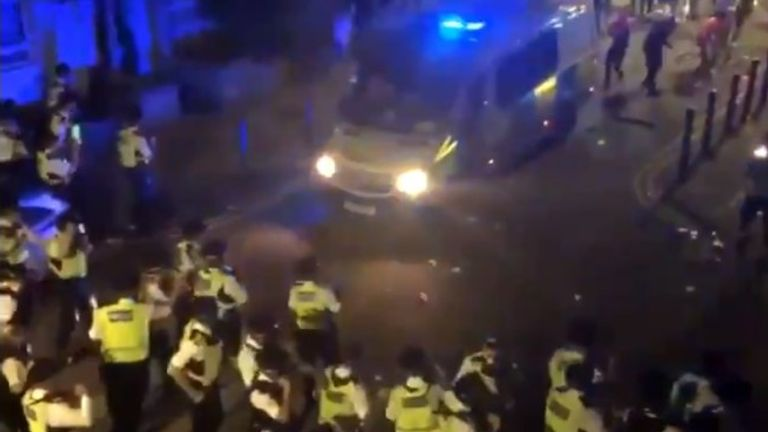 Police were seen retreating as the crowd threw bottles and other objects at them