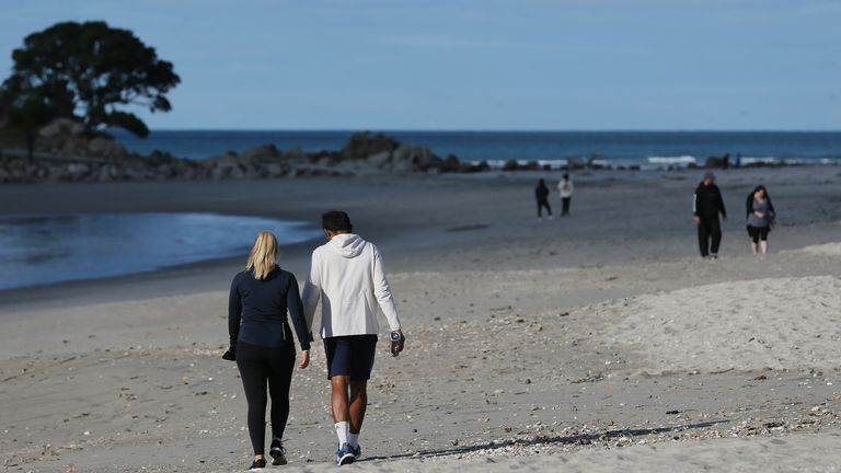People walk on the beach in Cambridge, New Zealand