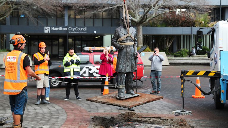 Workers remove a controversial statue of Captain John Hamilton from Civic Square in Hamilton , New Zealand