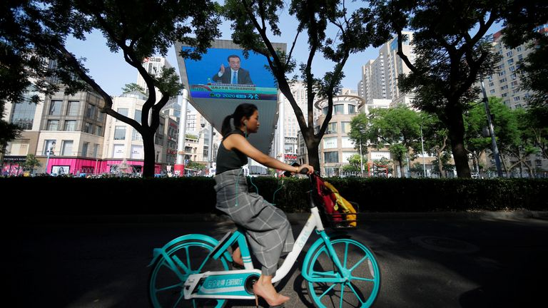 A woman cycles past a screen showing a news conference in Beijing